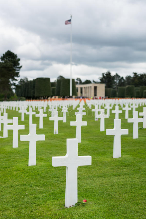 American Cemetery at Normandy. France,Cross of an unknown soldier.American flags waving royalty free stock photos