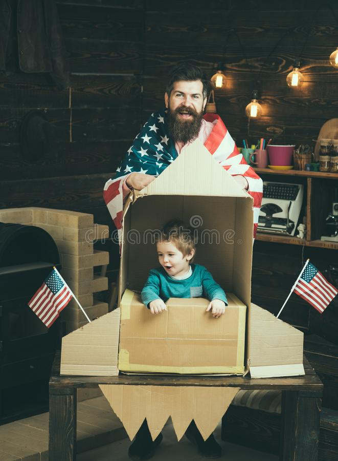American cheerful family with usa flags play with rocket made out of cardboard box. Child cute boy play cosmonaut royalty free stock image