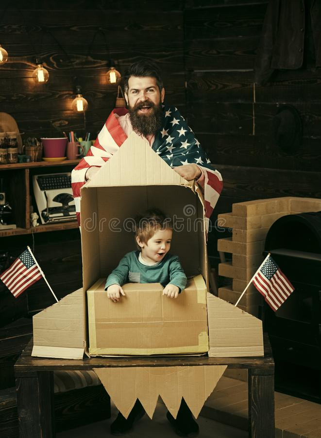 American cheerful family with usa flags play with rocket made out of cardboard box. Child cute boy play cosmonaut stock photography