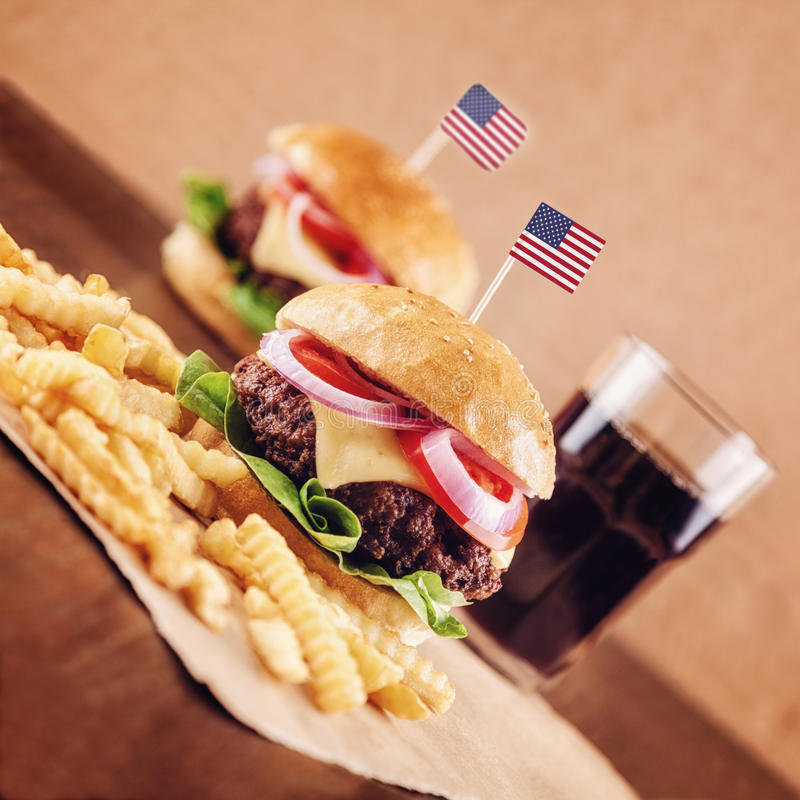 American Cheese Burger with French Fries and Cola. American Ground beef Cheese Burger with Lettuce,Tomato and Red Onion with French Fries and glass of Cola stock photos