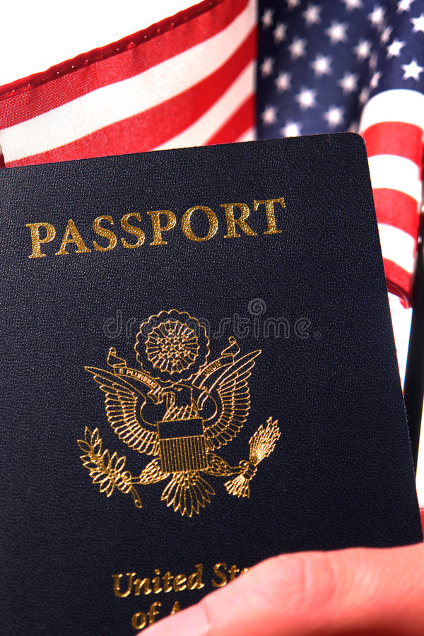 American Citizenship Passport and US Flag in Hand. Hand of a proud American citizen holding a United States of America passport and a US flag to show his new USA stock image