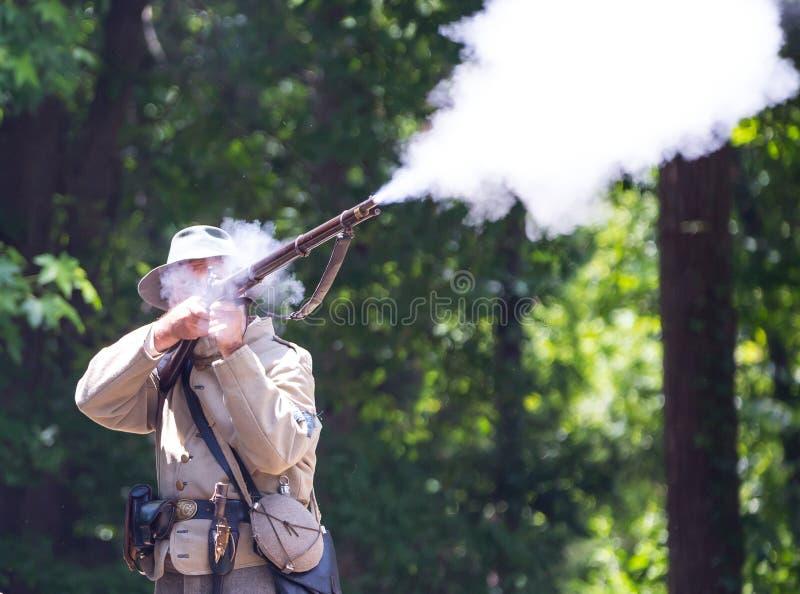 American Civil War Battle Reenactment. HUNTERSVILLE, NC - JUNE 1, 2019 USA:  Closeup of a reenactor in a Confederate army uniform firing his rifle during an stock images