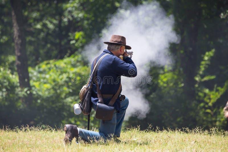 American Civil War Battle Reenactment. HUNTERSVILLE, NC - JUNE 1, 2019 USA:  A reenactors in a Union army uniform fires his rifle duirng an American Civil War royalty free stock photos