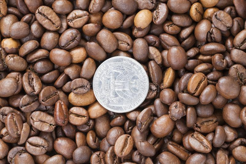 American coin. Beautiful and fragrant fried whole grains of coffee, closeup, top view, on coffee lies the reverse upward American coin in a quarter of a dollar stock photos