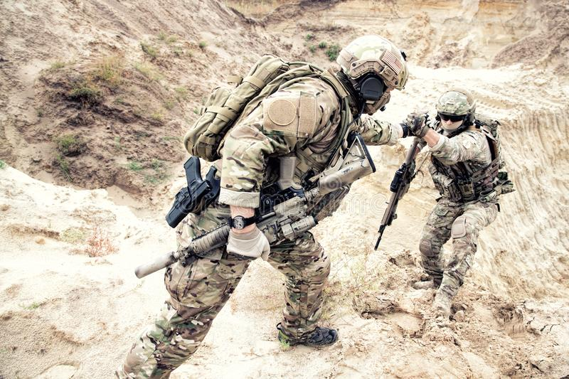 American commando helping friend to climb on dune royalty free stock photography