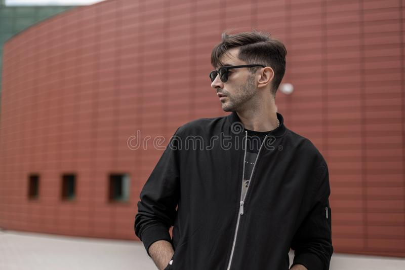 American cool young hipster man in a fashionable jacket in stylish sunglasses with trendy hairstyle walks in the city. On a summer day. Handsome guy model near stock images