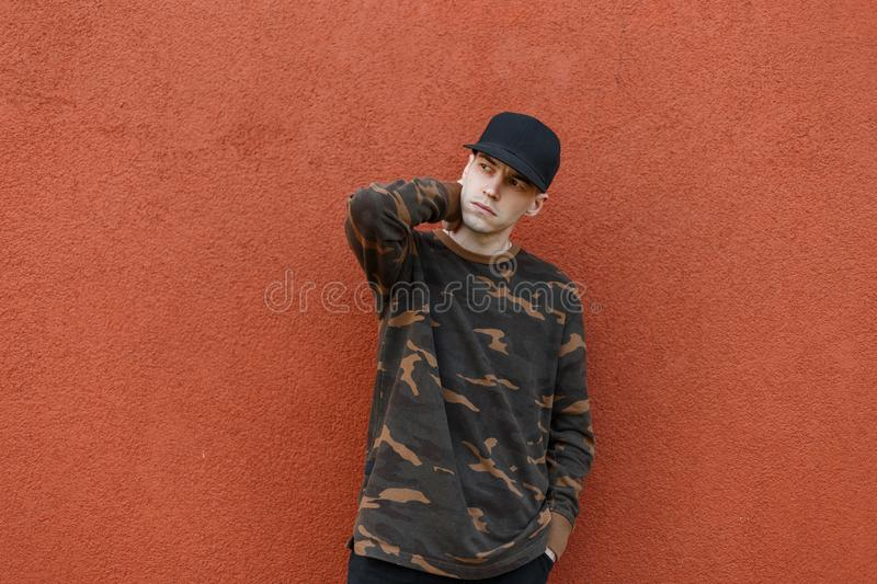 American cool young man in a fashionable cap in a green military shirt in jeans posing near a vintage wall  pantone color 2019 stock photo
