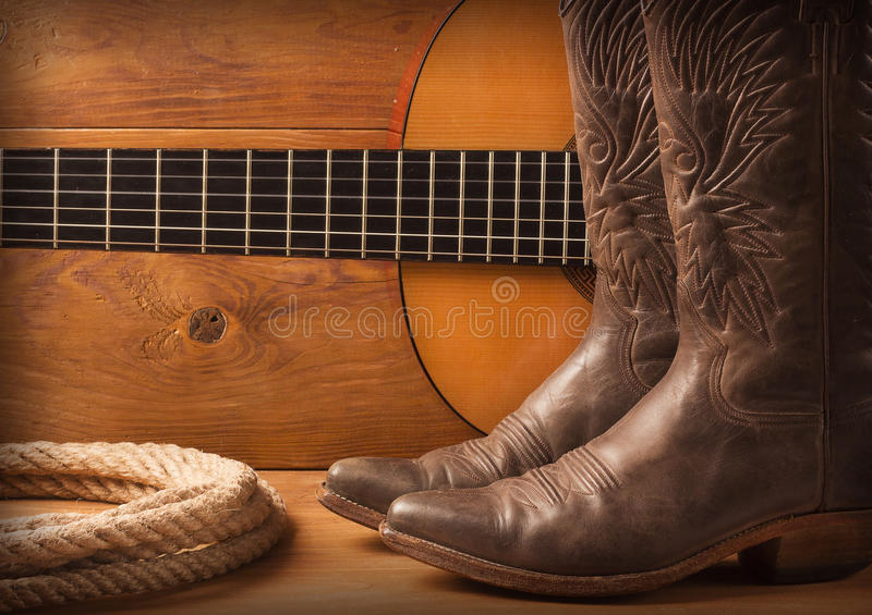 American Country music with guitar and cowboy shoes on wood text. Country music with guitar and cowboy shoes on wood texture background royalty free stock images