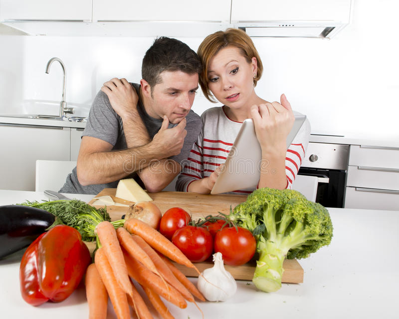 American couple in domestic kitchen wife following recipe in digital pad working together with husband. Young happy American couple working in domestic kitchen stock images