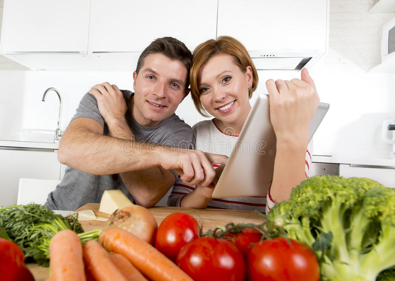 American couple in domestic kitchen wife following recipe in digital pad working together with husband. Young happy American couple working in domestic kitchen royalty free stock images
