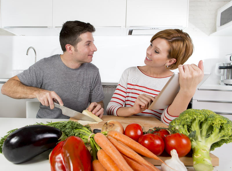 American couple in domestic kitchen wife following recipe in digital pad working together with husband. Young happy American couple working in domestic kitchen stock photos