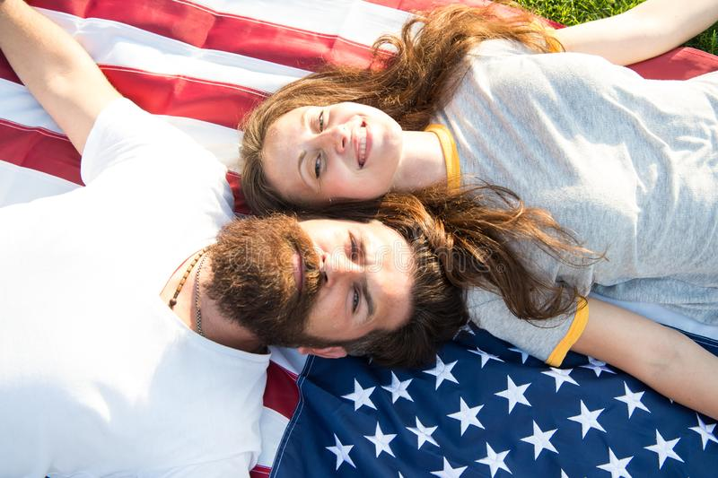 American couple relaxing on USA flag outdoors. Independence day. National holiday. Bearded hipster and girl in love. 4th. Of July. American tradition. History royalty free stock photography