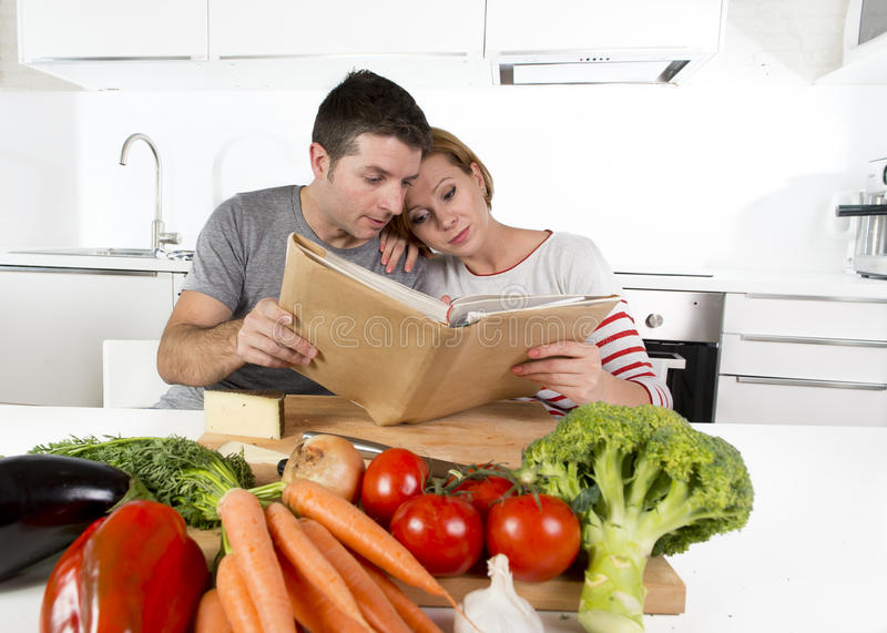 American couple working in domestic kitchen following recipe reading cookbook together. Young happy American couple working in domestic kitchen following recipe stock photography