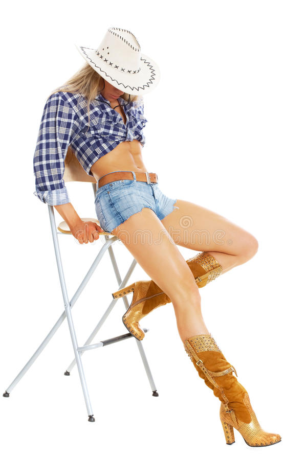 American cowgirl. Portrait of a model posing in cowgirl clothing posing on a chair stock image