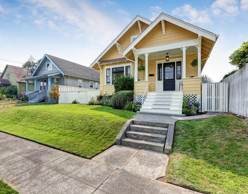 American craftsman home with yellow exterior paint. American craftsman home with yellow exterior paint and well kept front garden. Northwest, USA royalty free stock image
