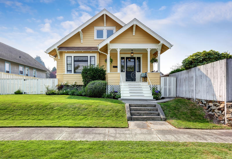 American craftsman home with yellow exterior paint. stock image