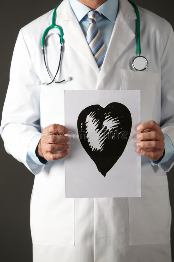 American doctor holding ink drawing of heart. Cropped portrait of American doctor holding ink drawing of heart royalty free stock photos