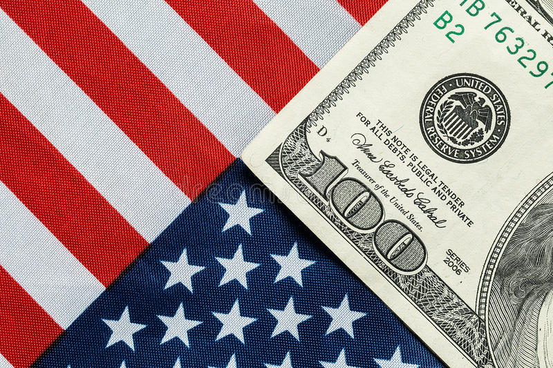 American dollar on the American flag. A hundred dollar bill in front of the American flag stock photography