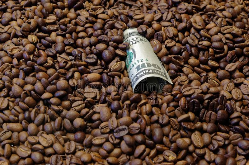 100 american dollar banknote laid in the roasted coffee beans. Close-up photo of one hundred american dollar banknote in the roasted coffee beans stock photos