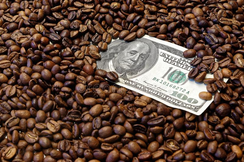 100 american dollar banknote in the roasted coffee beans. 100 american dollar banknote lies in roasted coffee beans as background royalty free stock photo