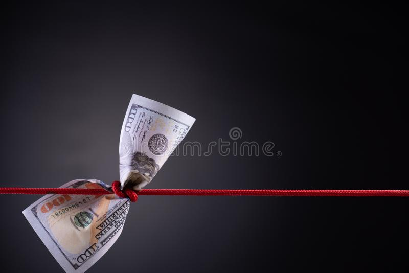 American dollar tied up in red rope knot on dark background with copy space. business finances, savings and bankruptcy concept stock photography