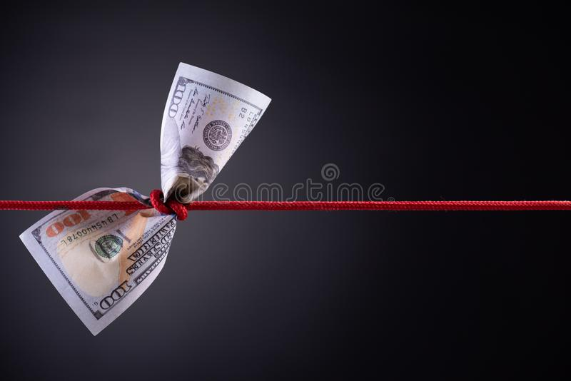 American dollar tied up in red rope knot on dark background with copy space. business finances, savings and bankruptcy concept.  stock image