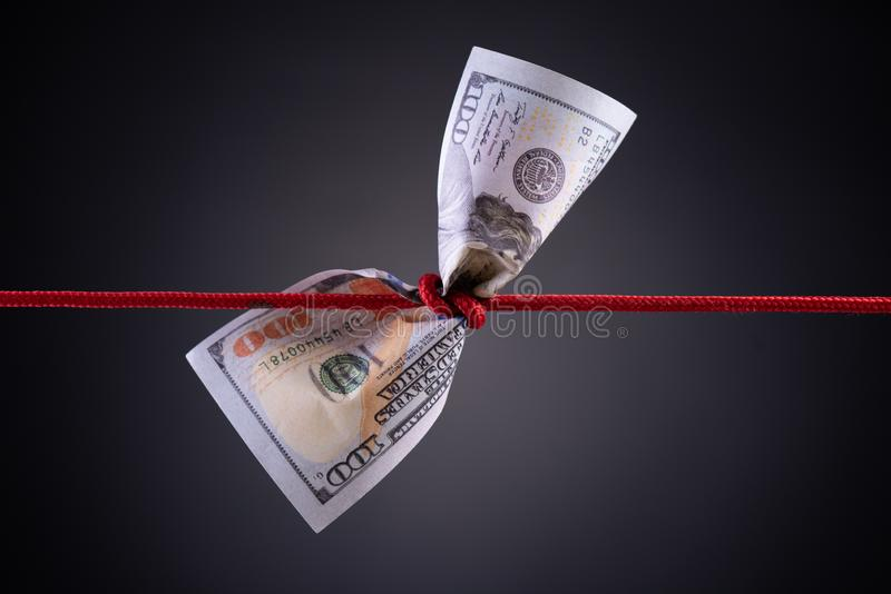 American dollar tied up in red rope knot on dark background with copy space. business finances, savings and bankruptcy concept.  royalty free stock images