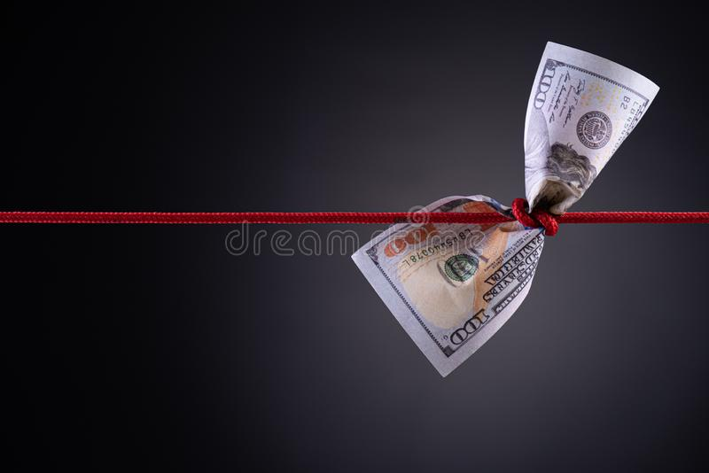 American dollar tied up in red rope knot on dark background with copy space. business finances, savings and bankruptcy concept.  stock photography