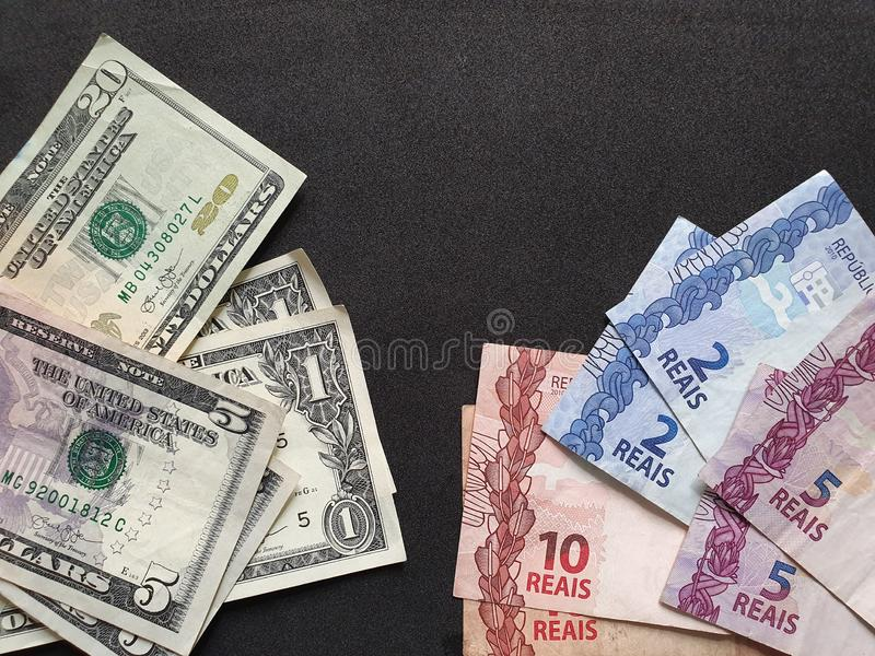American dollars bills and Brazilian banknotes on the black background. Commerce, exchange, travel, trade, trading, value, buy, sell, profit, price, rate, cash stock image