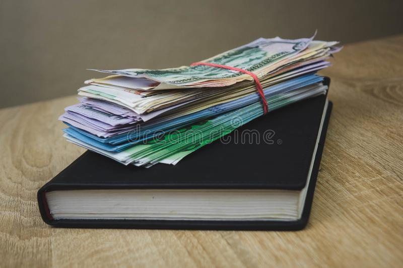 American dollars, euros, rubles are on a black notebook. The concept of a financial plan for the year, investment or saving money stock photography