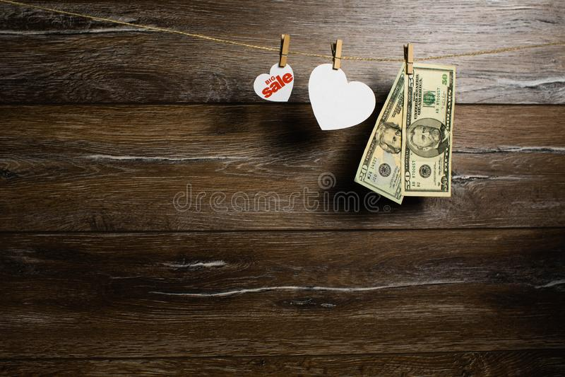 American dollars in two banknotes and hearts for big sale hanging with clothespins. Holiday sale. American dollars in two banknotes and hearts for big sale stock image