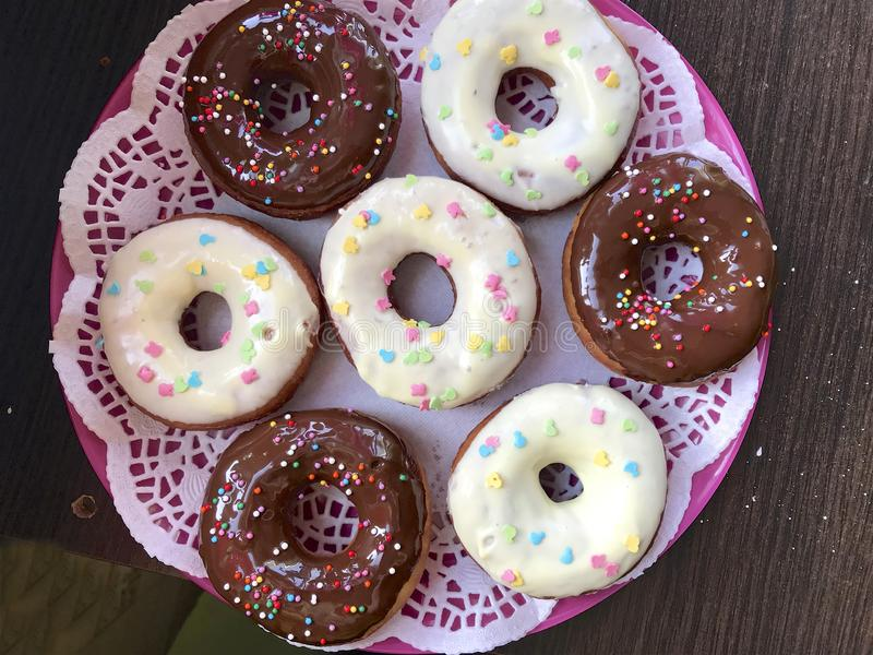 American donuts, glazed with melted chocolate and decorated with sprinkling, lie on a platter royalty free stock image
