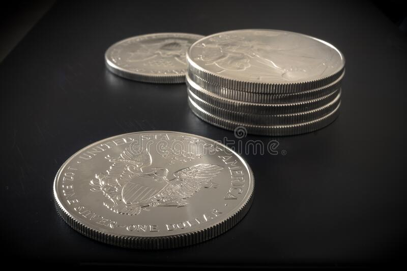 American Eagle Silver Dollars. Detailed image of Silver Eagle Dollars on dark background. Each coin is one troy ounce of pure silver stock photo
