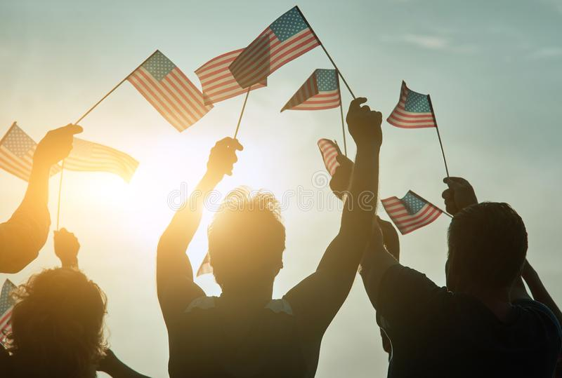American elections concept. People raising usa flags up to the sky royalty free stock photography