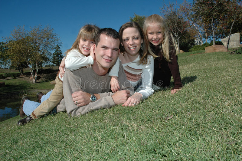 American Family. An american family take their portraits in nature laying on the grassy ground. A family of four with two daughters and their parents royalty free stock images