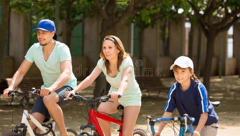 American family riding bicycles in park togetherness stock images