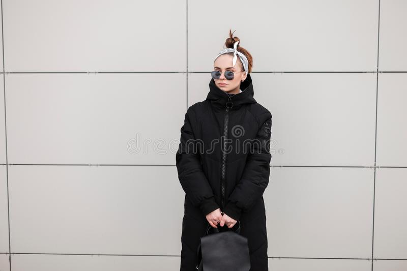 American fashionable young hipster woman in a long winter stylish black coat with a leather backpack with a bandana in sunglasses. Near a modern building stock photo