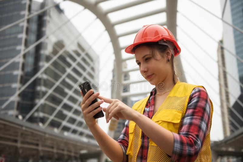 American female engineer using smartphone at site royalty free stock photo