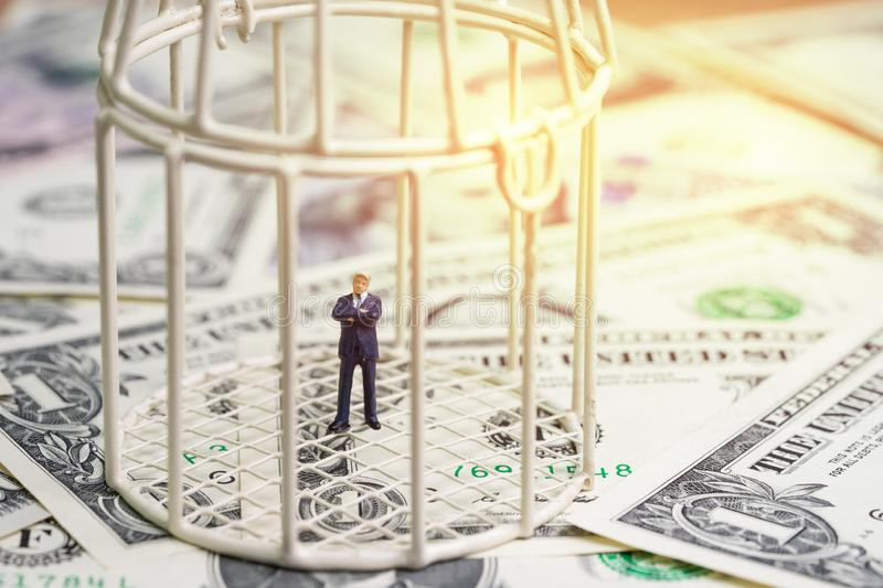 American first, financial war under protection, miniature businessman president inside birdcage on pile of US dollar banknotes, m royalty free stock photography