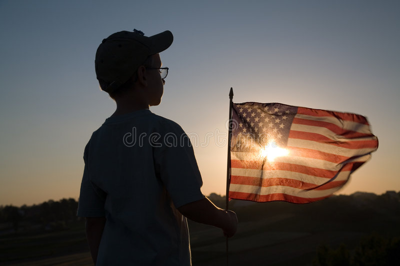 American Flag. Boy with American flag at sunset