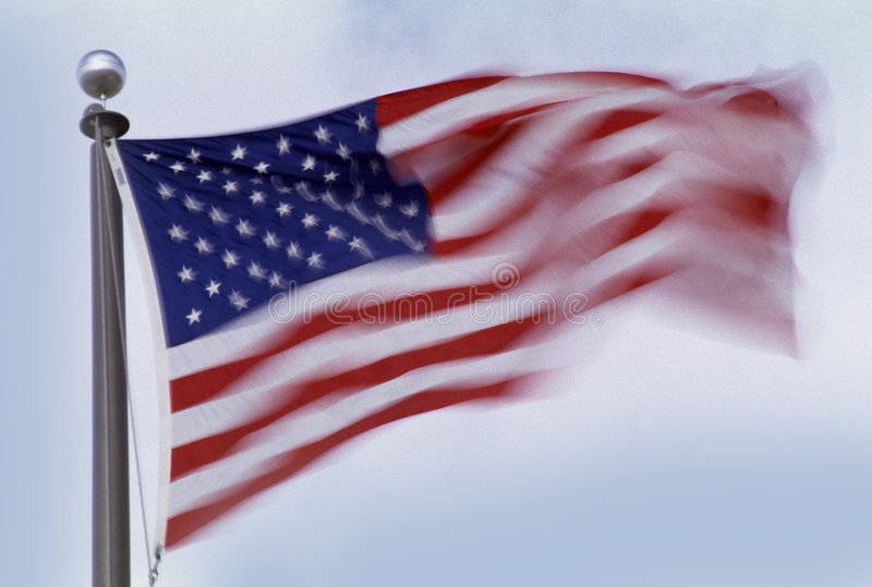 American Flag. On pole blowing in the wind with motion on light blue background stock photo