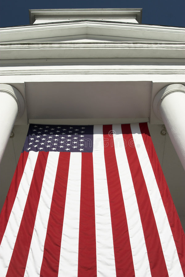 American flag. Large American flag hanging from greek revival building royalty free stock photos