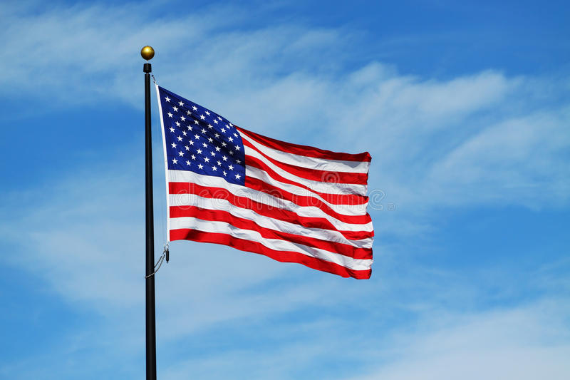 American Flag. The American Flag waving against a cloudy blue sky stock photography