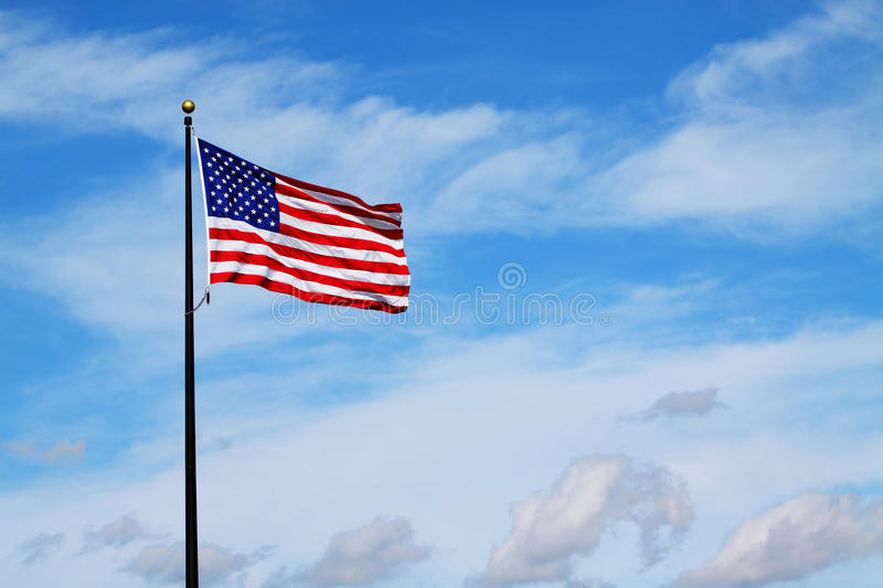 American Flag. The American Flag waving in the wind against a cloudy blue sky stock photos