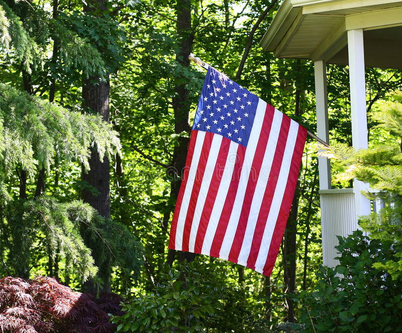 American Flag. Flying from porch in wooded setting royalty free stock photo