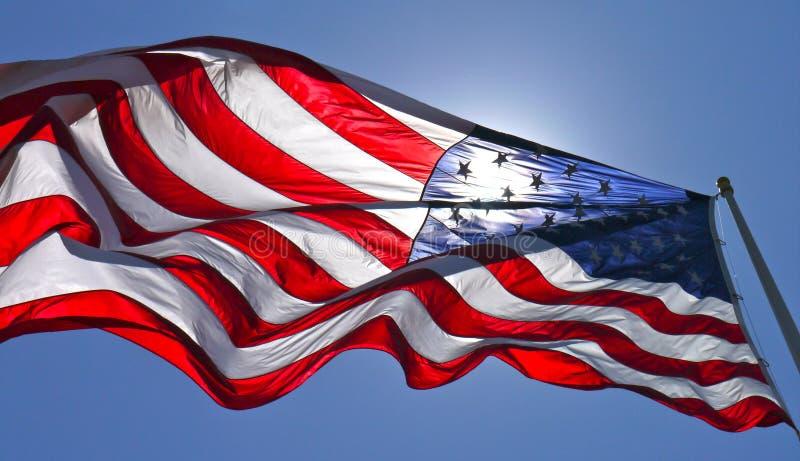 American flag. Sun shining through American flag flying in blue sky stock image