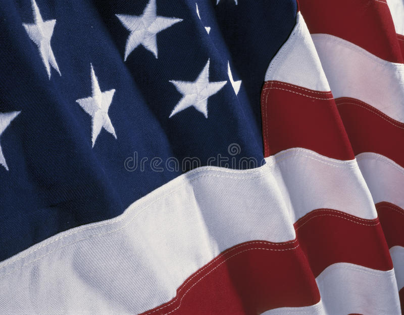 American flag. This is an American flag with waves folding over the blue field of stars and red and white stripes stock photos