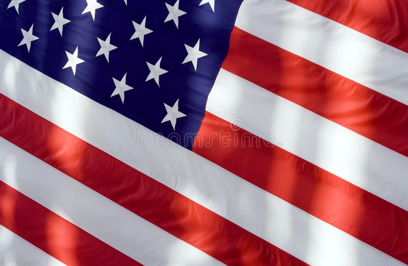 American Flag. A closeup view of an American flag bathed in sunlight with shadows royalty free stock photography