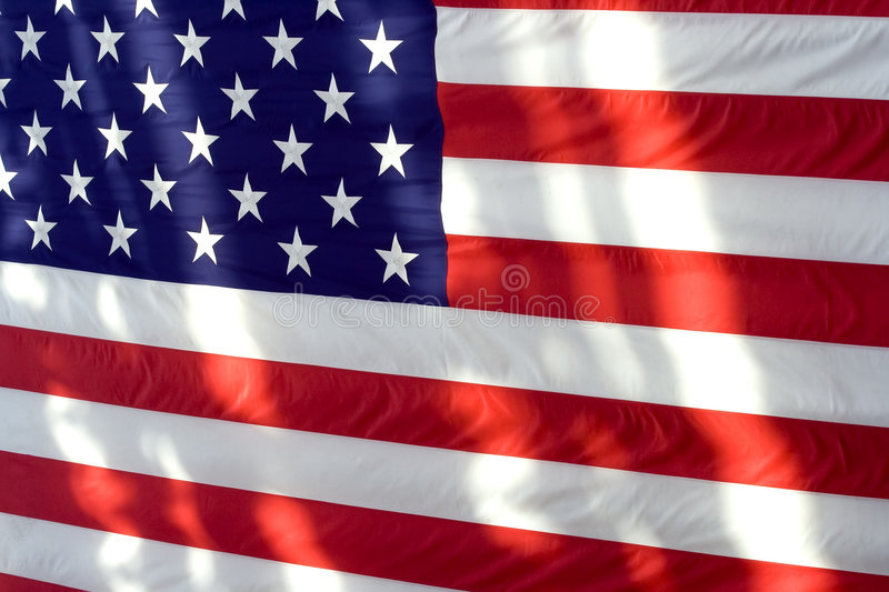 American Flag. A closeup view of an American flag bathed in sunlight with shadows royalty free stock image