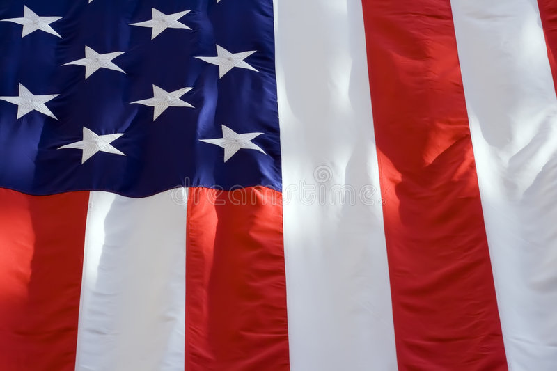 American Flag. A closeup view of an American flag bathed in sunlight with shadows stock images